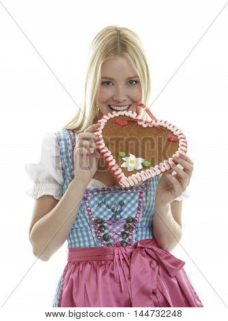 Woman bites in an empty German Gingerbread heart