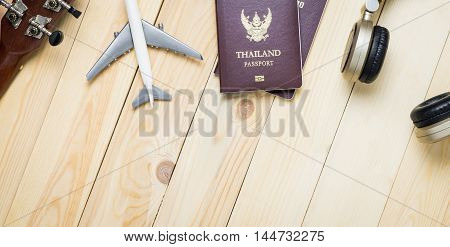 Travel objects equipments on wooden table with copy space. Travel Banner with passport, plane, headphone for summer music vacation travel.
