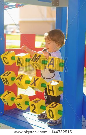 Little toddler boy playing on the playground with cubes. On the yellow cubes painted letters