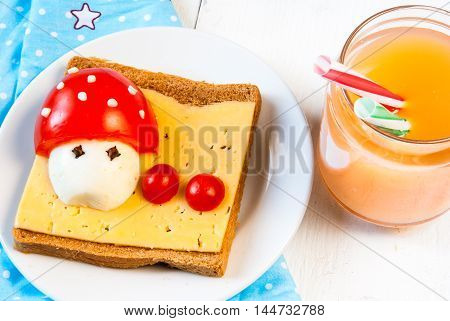 Cute breakfast for kid: a sandwich with a funny cartoon mushroom with cheese, eggs and tomatoes