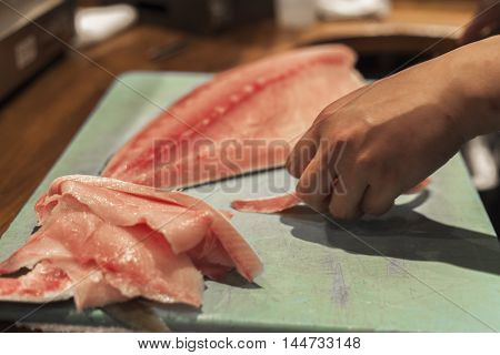 A sushi chef prepares fish for the day.