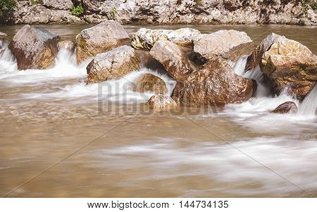 River flowing through rocks. Long exposure of white water rapids and waves along section of the Gradac river, Serbia