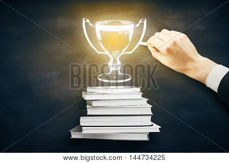 Leadership concept with businessman hand drawing abstract illuminated winner's cup above book stack on blackboard background