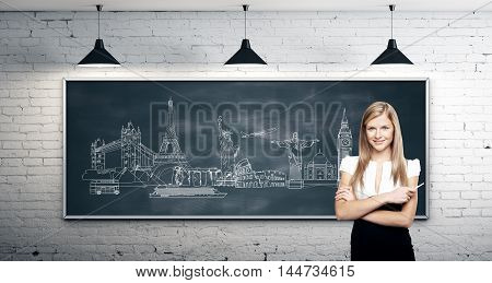 Travel concept with confident businesswoman standing against chalkboard with monuments drawing