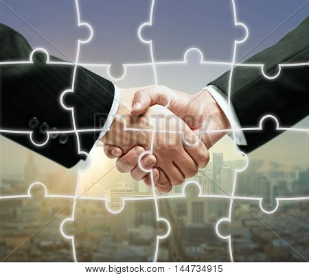 Businesspeople shaking hands on city background with puzzle piece pattern. Teamwork concept