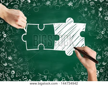 Male hands drawing puzzle pieces and success icons sketch on chalkboard background. Business partnership sketch