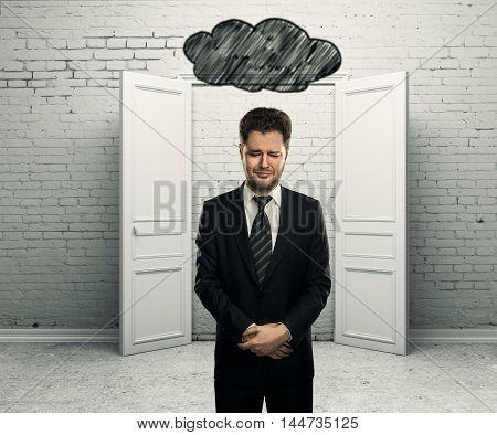 Sad businessman with abstract dark cloud sketch above head in white brick interior