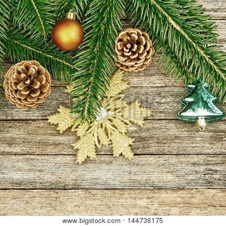 New Year or Christmas background: fir branches colorful glass balls and golden snow-flake cones over old wooden backdrop top view copy space tinted photo