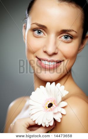 Gorgeous woman with herbera looking at camera with smile over grey background