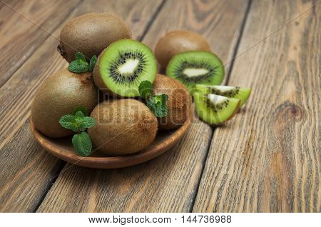 Fresh juicy ripe kiwi in a wooden plate on a wooden background
