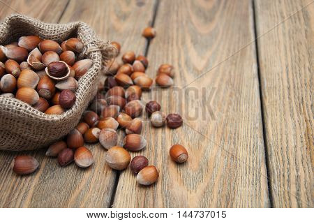 Hazelnuts in a small bag on the old board