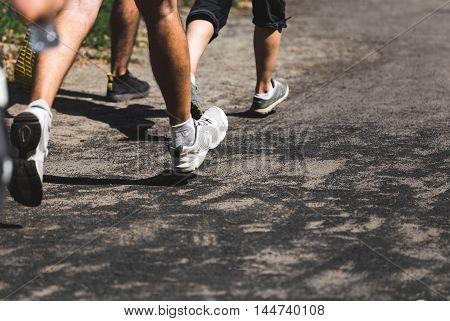 Running people on crossfit competition, feet on the road close up photo.