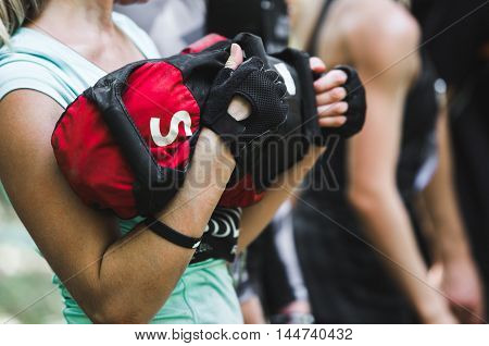 Close-up of woman training at crossfit center with sandbag.