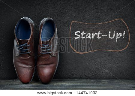 Start-up text on black board and business shoes on wooden floor