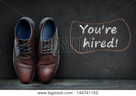 You are hired text on black board and business shoes on wooden floor