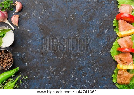 Frame of pork for barbeque and vegetable on the spotty black surface