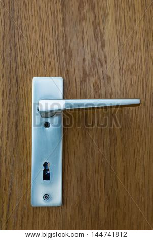 Metal Chrome European Doorhandle Wood Texture Background