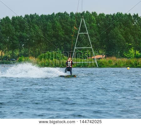 Wakeboarder holding a cable tow and riding water surface