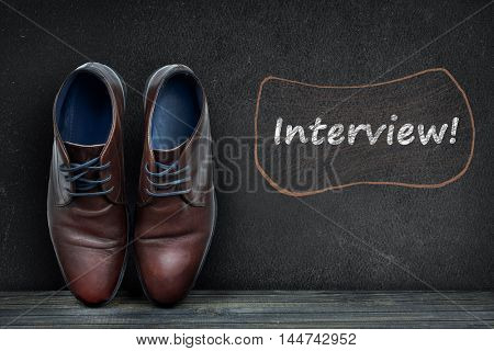 Interview text on black board and business shoes on wooden floor