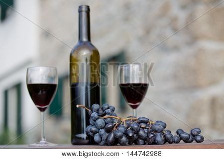 wine bottle and grapes on wooden table outdoor, focus on the grapes