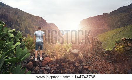 man looks through mountains to the sunset of Tenerife, canary islands