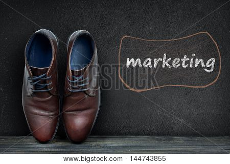 Marketing text on black board and business shoes on wooden floor