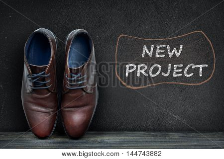 New Project text on black board and business shoes on wooden floor