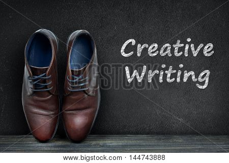 Creative Writing text on black board and business shoes on wooden floor