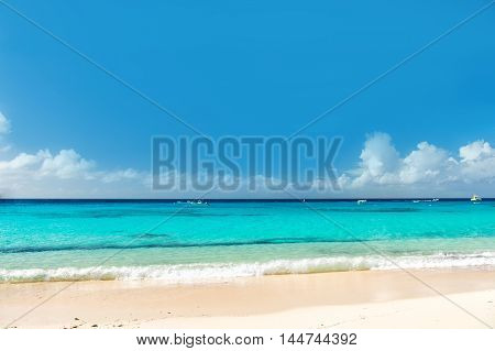 Beautiful marine view on sea coast line with clean wavy surf water on sandy beach horizon and cloudy blue sky at sunny day