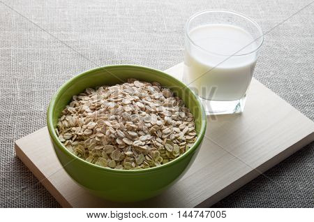 Green Bowl Of Dry Cereal And A Glass Of Milk