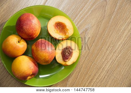 Healthy organic food, healthy fruits peaches. Ripe and tasty and juicy peaches lie on a plate on a wooden table