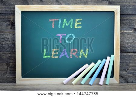 Time to learn text on school board and chalk on wooden table