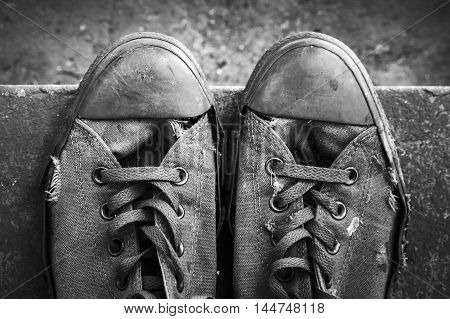 Pair Of Grungy Sneakers Standing On Concrete