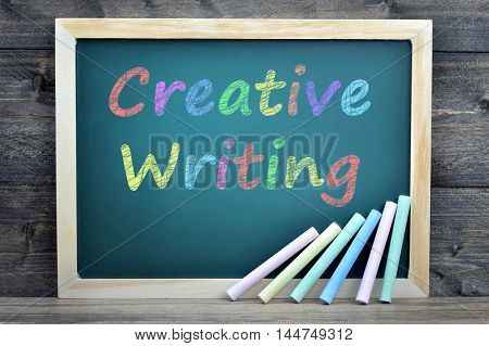 Creative Writing text on school board and chalk on wooden table