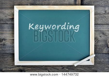 Keywording text on school board and chalk on wooden table