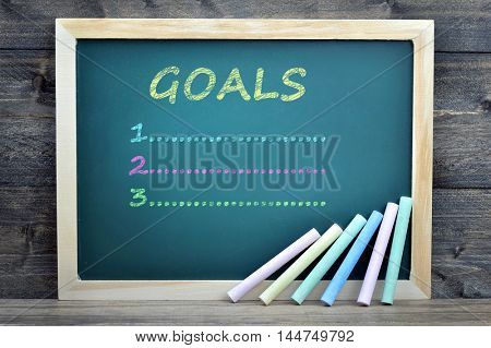 Goals text on school board and chalk on wooden table