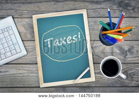 Taxes text on school board and coffee on desk