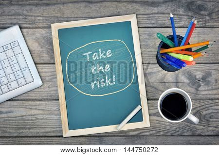 Take the risk text on school board and coffee on desk