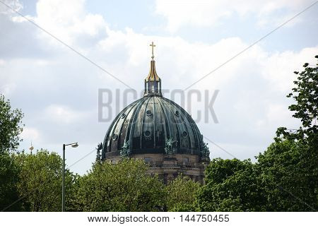 The cupola of the Berlin Cathedral behind bushes and trees.