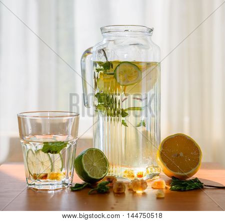 Pitcher of homemade lemonade with glass and scattered ingredients on window background. Healthy salvation from the heat.