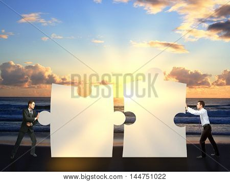 Two businessmen pushing puzzle pieces together on sea background with setting sun. Cooperation concept