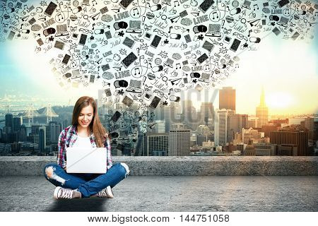 Happy casual woman on rooftop using laptop with abstract media icon above on city background. Social networks concept
