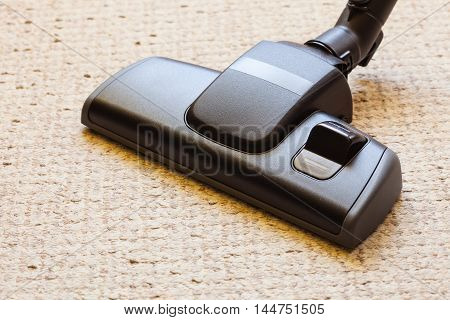 background with copy space. closeup cleaning with black vacuum cleaner hoover dirty dusty floor beige carpet. housework.
