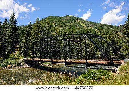Black steel bridge spans the Gallatin River in Montana. Sign on bridge calls it the