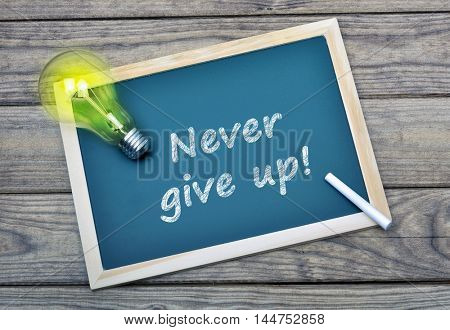 Never give up text on school board and glowing light bulb