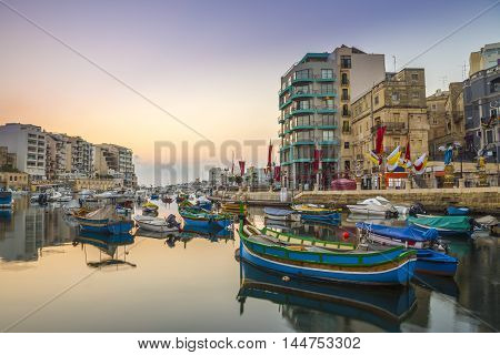 St.Julian's Malta - Traditional colorful Luzzu fishing boats at Spinola bay at sunrise