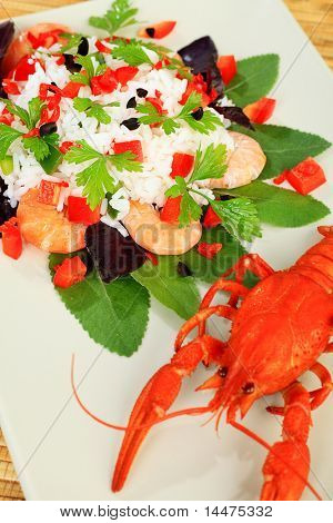 A dish with steamed white rice,  shrimps and boiled crawfish.