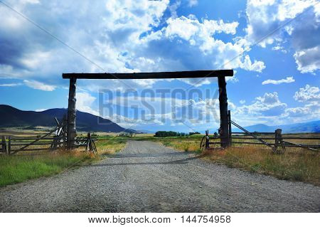 Popular architecture for a country entry this weathered log construction spans driveway to ranch. Montana ranches often use this type of rustic architecture.