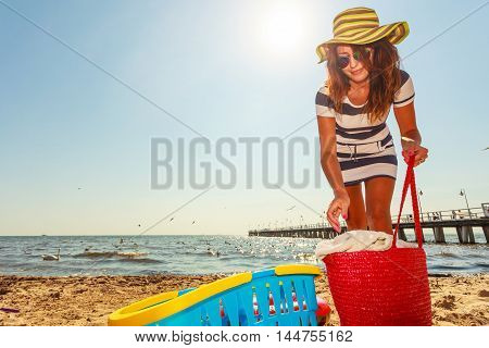 Relaxation and leisure. Attractive mid aged woman resting on beach. Female tourist relax near to water place on nature.