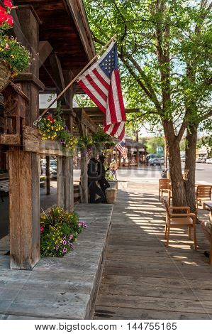 wooden sidewalk with American flags and sculptured silhouettes in Winthrop Washington State USA